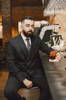 Деловой человек в пабе с коктейлем