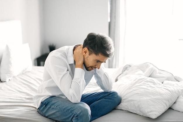 Деловой человек в рубашке и джинсах касается его шеи руками на светлом фоне в помещении. фото высокого качества