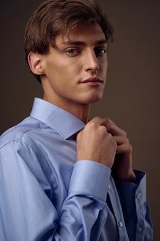 シャツを着たビジネスマンは彼のネクタイをまっすぐにする公式の自信