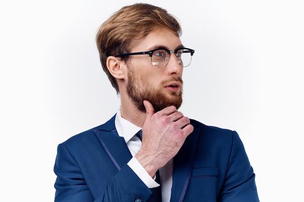 スーツと眼鏡のビジネスマンは、明るい背景の青いジャケットで彼の顔の近くに彼の手を保持します。