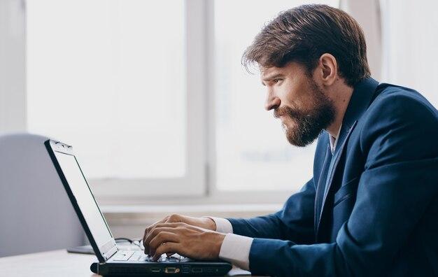 窓の近くにノートパソコンを持ってテーブルでスーツを着たビジネスマン