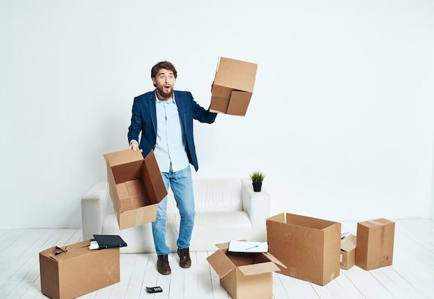 Деловой человек в костюме коробки в руках, собирая движущиеся вещи