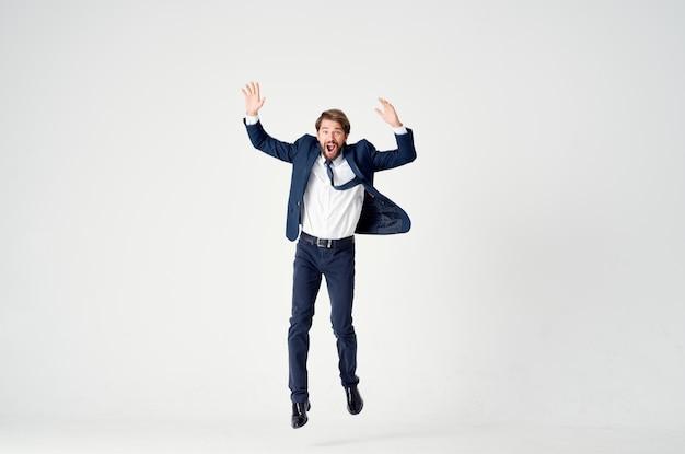 完全な高さの勝利をジャンプするスーツの感情のビジネスマン