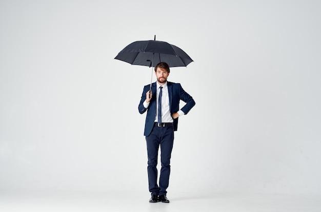 雨から傘のエレガントなスタイルの保護を保持しているスーツのビジネスマン