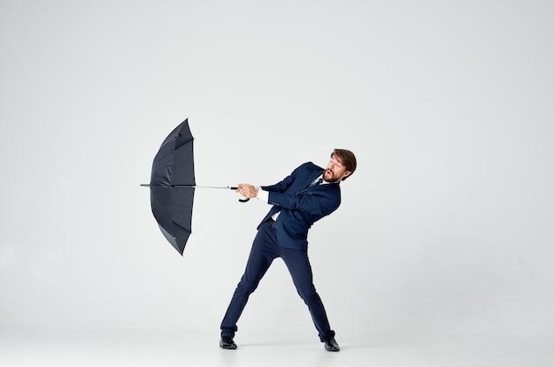 Деловой человек в костюме, держащем зонтик, элегантный стиль защиты от дождя