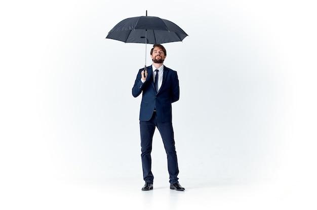 傘を持っているスーツのビジネスマンエレガントなスタイルの雨よけ