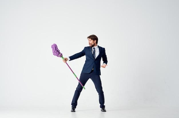 Деловой человек в костюме менеджер работает уборка шваброй. фото высокого качества