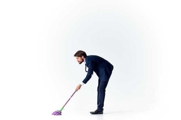 Деловой человек в костюме менеджера работает, убирая шваброй