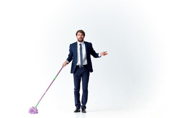 スーツマネージャーのビジネスマンはモップで掃除をします