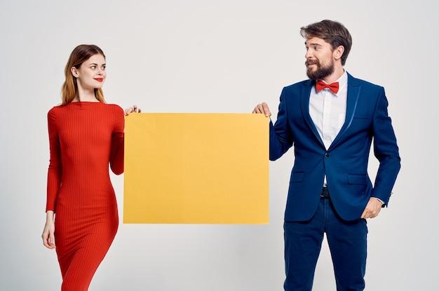 赤いドレスの黄色いモックアップポスターの女性の隣にスーツを着たビジネスマン