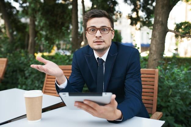 Деловой человек в костюме на улице в кафе