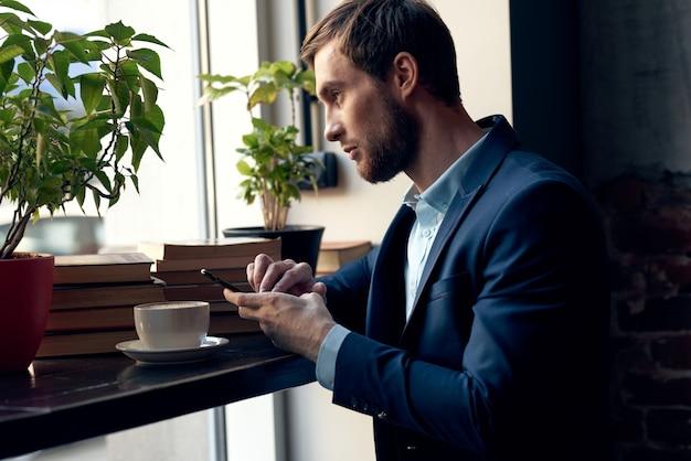 カフェレジャー朝食の専門家のテーブルに座ってスーツを着たビジネスマン