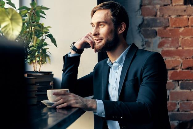 カフェの仕事の余暇に座っているスーツを着たビジネスマン