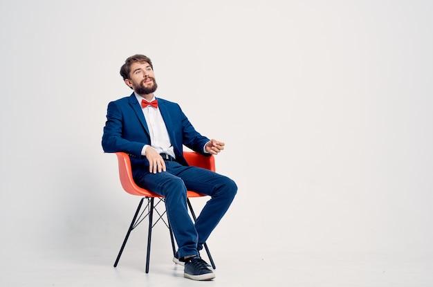 Деловой человек в костюме, сидя на стуле в современном стиле студии