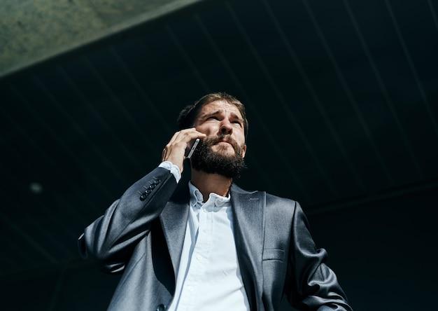 電話で話しているスーツのビジネスマン屋外ビジネスマネージャーエグゼクティブ