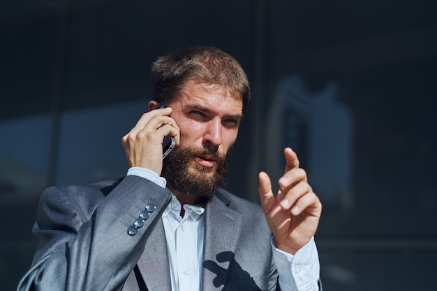 Деловой человек в костюме разговаривает по телефону на открытом воздухе бизнес-менеджер исполнительный