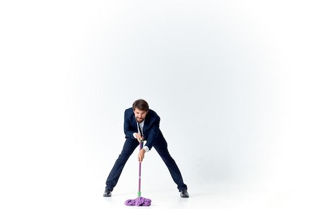 Деловой человек в костюме моет полы с шваброй, убирая офис-менеджер