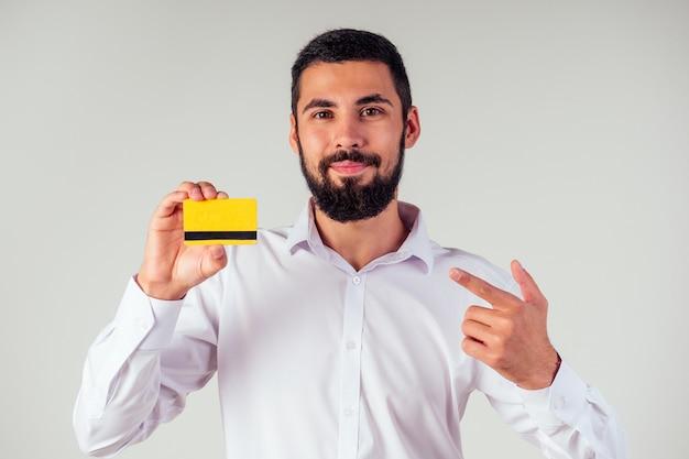 Деловой человек в белой рубашке, держа кредитную карту yellpw. смотрю в камеру, улыбаюсь. черная пятница продажа и потратить деньги концепция