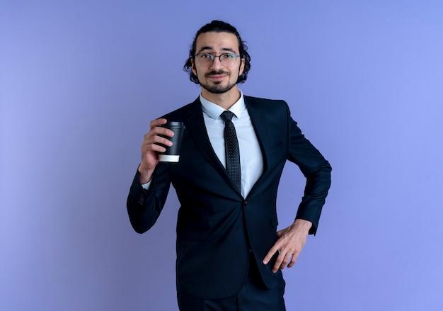 青い壁の上に立っている自信を持って表情で正面を向いてコーヒーカップを保持している黒いスーツとメガネのビジネスマン