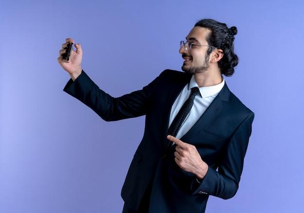 青い壁の上に元気に立って笑って横に指で指しているクレジットカードを保持している黒いスーツとメガネのビジネスマン