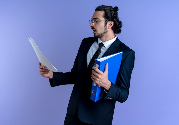 파란색 벽 위에 서 심각한 얼굴로 문서를보고 폴더를 들고 검은 양복과 안경 비즈니스 남자