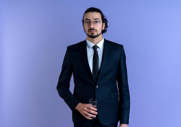 青い壁の上に立っている真面目な顔で正面を向いて水のガラスを保持している黒いスーツとメガネのビジネスマン