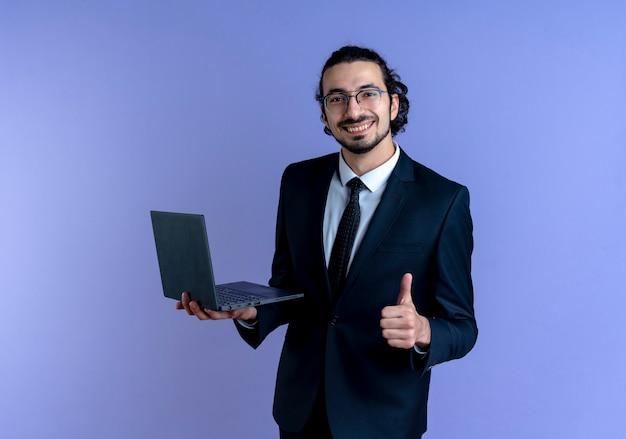 青い壁の上に立って親指を見せて笑顔で正面を見てラップトップコンピューターを保持している黒いスーツと眼鏡のビジネスマン