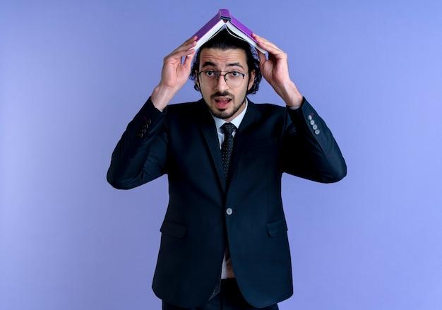 검은 양복과 그의 머리 위에 노트북을 들고 안경에 비즈니스 남자는 파란색 벽에 서 혼란 스 러 워 찾고