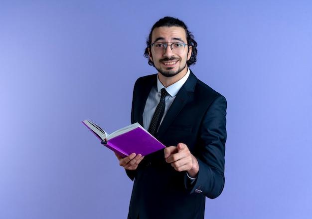 青い壁の上に元気に立って笑顔の人差し指でノートを指している黒いスーツとメガネのビジネスマン