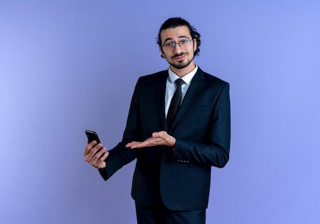 青い壁の上に立って自信を持って笑顔の彼の手の腕を提示するスマートフォンを保持している黒いスーツとメガネのビジネスマン