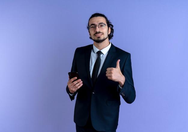 青い壁の上に立って笑顔で親指を示すスマートフォンを保持している黒いスーツとメガネのビジネスマン