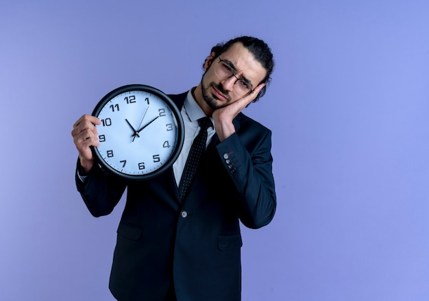 青い壁の上に立って睡眠ジェスチャーを作る疲れて過労に見える壁時計を保持している黒いスーツと眼鏡のビジネスマン