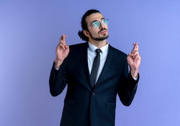 Деловой человек в черном костюме и очках смотрит в сторону, загадывая желание, скрещивая пальцы, стоя над синей стеной