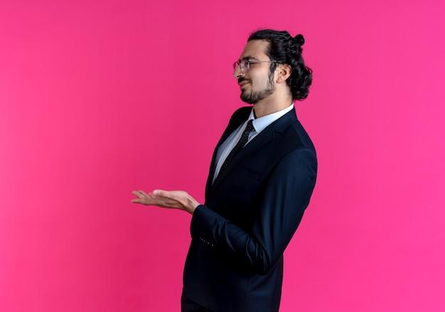 Деловой человек в черном костюме и очках смотрит в сторону с вытянутой рукой и задает вопрос, стоя над розовой стеной
