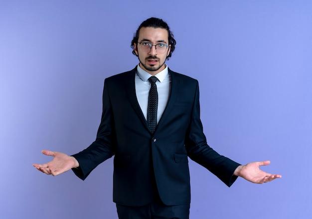 파란색 벽 위에 서있는 측면에 혼란스럽고 불확실한 확산 팔을 찾고 검은 양복과 안경 비즈니스 남자