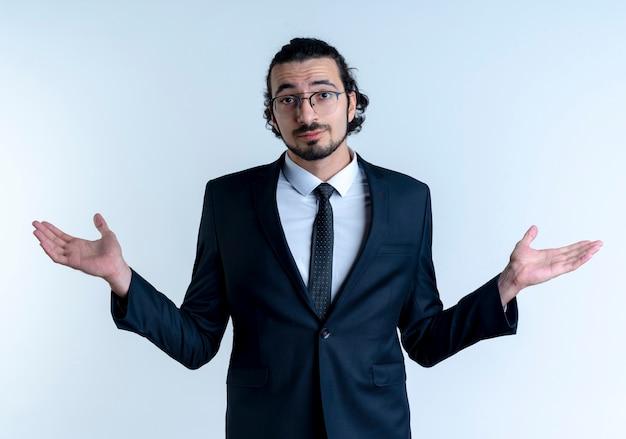 흰 벽 위에 서있는 측면에 혼란스럽고 불확실한 확산 팔을 찾고 검은 양복과 안경에 비즈니스 남자