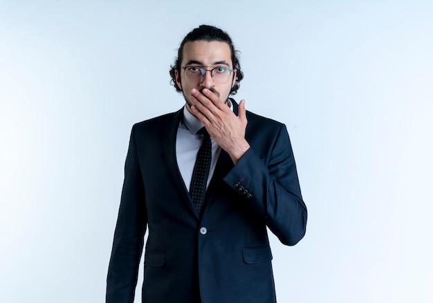 검은 양복과 안경에 비즈니스 남자가 정면을보고는 흰 벽 위에 서있는 손으로 입을 덮고 충격을 받았다.