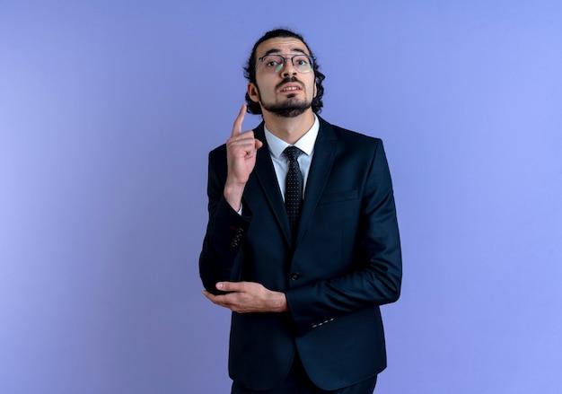 青い壁の上に立っていることを忘れないように自分自身を思い出させる人差し指を示す正面を向いている黒いスーツと眼鏡のビジネスマン