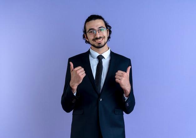 黒いスーツと眼鏡をかけたビジネスマンは、青い壁の上に立って親指を元気に見せて笑顔で正面を向いています
