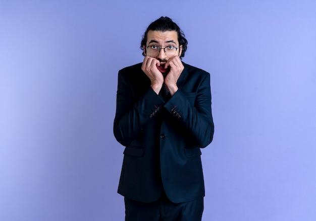 黒いスーツと眼鏡をかけたビジネスマンが青い壁の上に立っているストレスと神経質な噛む爪を正面から見ています