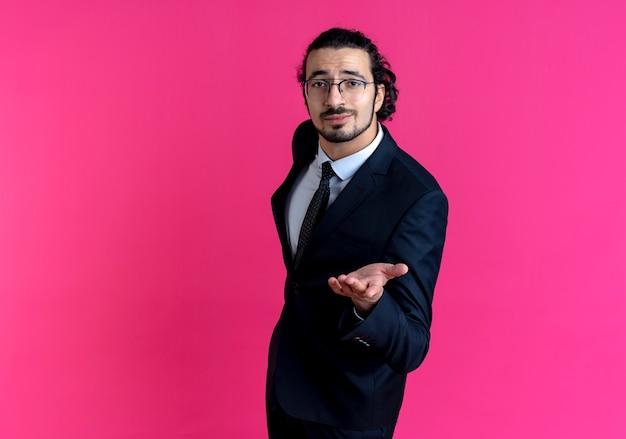 Деловой человек в черном костюме и очках смотрит вперед с вытянутой рукой, задавая вопрос, стоя над розовой стеной