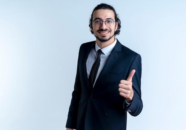 Деловой человек в черном костюме и очках смотрит вперед с уверенным выражением лица, улыбаясь, показывает палец вверх, стоя над белой стеной 2
