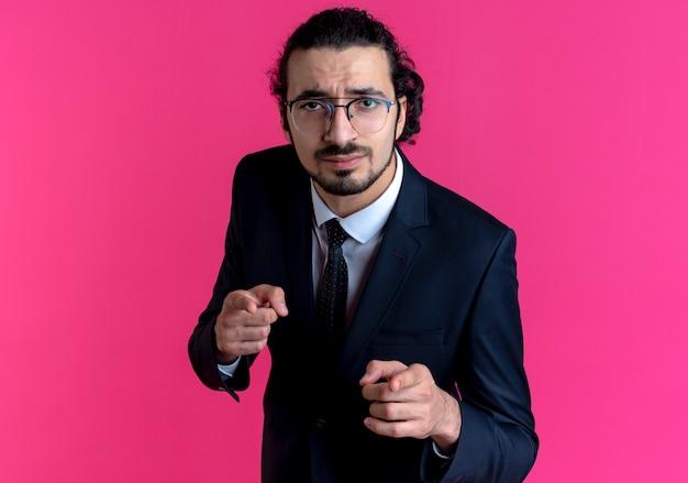검은 양복과 분홍색 벽 위에 서있는 앞쪽에 검지 손가락으로 가리키는 얼굴을 찡그린 얼굴로 정면을 바라 보는 안경 비즈니스 남자