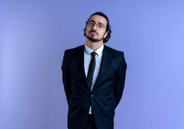검은 양복과 파란색 벽 위에 서있는 얼굴을 찡그린 얼굴로 정면을 찾고 안경 비즈니스 남자