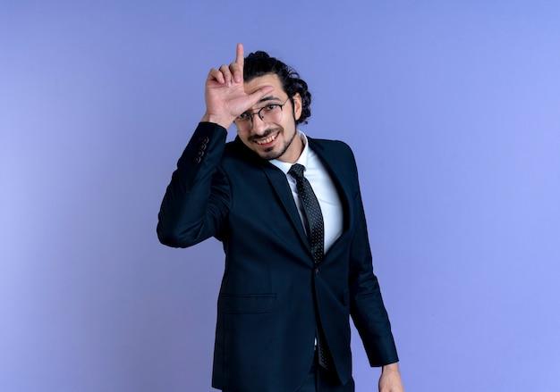 青い壁の上に元気に立って笑顔で頭上に敗者のサインと正面を向いている黒いスーツとメガネのビジネスマン