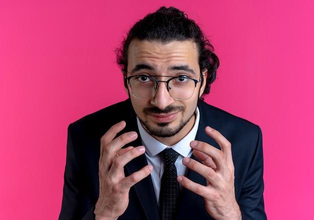 검은 양복과 안경을 들고있는 비즈니스 남자가 분홍색 벽 위에 서서 불쾌한 표정을 짓고있는 팔을 올린 채로 정면을 바라보고 있습니다.