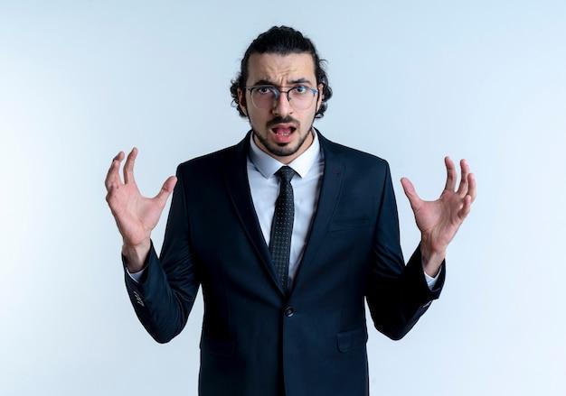 흰 벽 위에 서있는 공격적인 표정으로 팔을 제기 검은 양복과 안경 앞에 비즈니스 남자