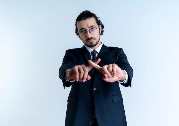 검은 양복과 흰 벽 위에 서있는 방어 제스처를 만드는 심각한 얼굴 횡단 검지 손가락으로 정면을 바라 보는 안경 비즈니스 남자