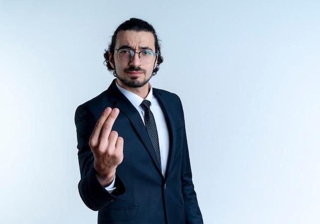 검은 양복과 흰 벽 위에 서있는 두 손가락을 보여주는 심각한 얼굴로 정면을 바라 보는 안경 비즈니스 남자