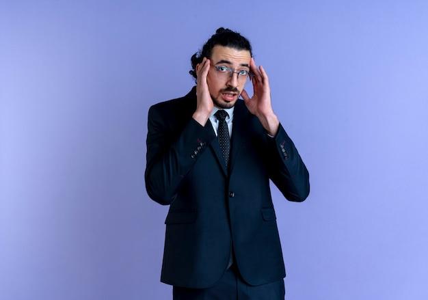 青い壁の上に立っている寺院に触れることを心配して正面を見て黒いスーツと眼鏡のビジネスマン